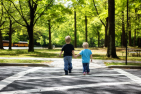 Two little boys hold hands while crossing the street. They are in a park filled with green trees in NJ.